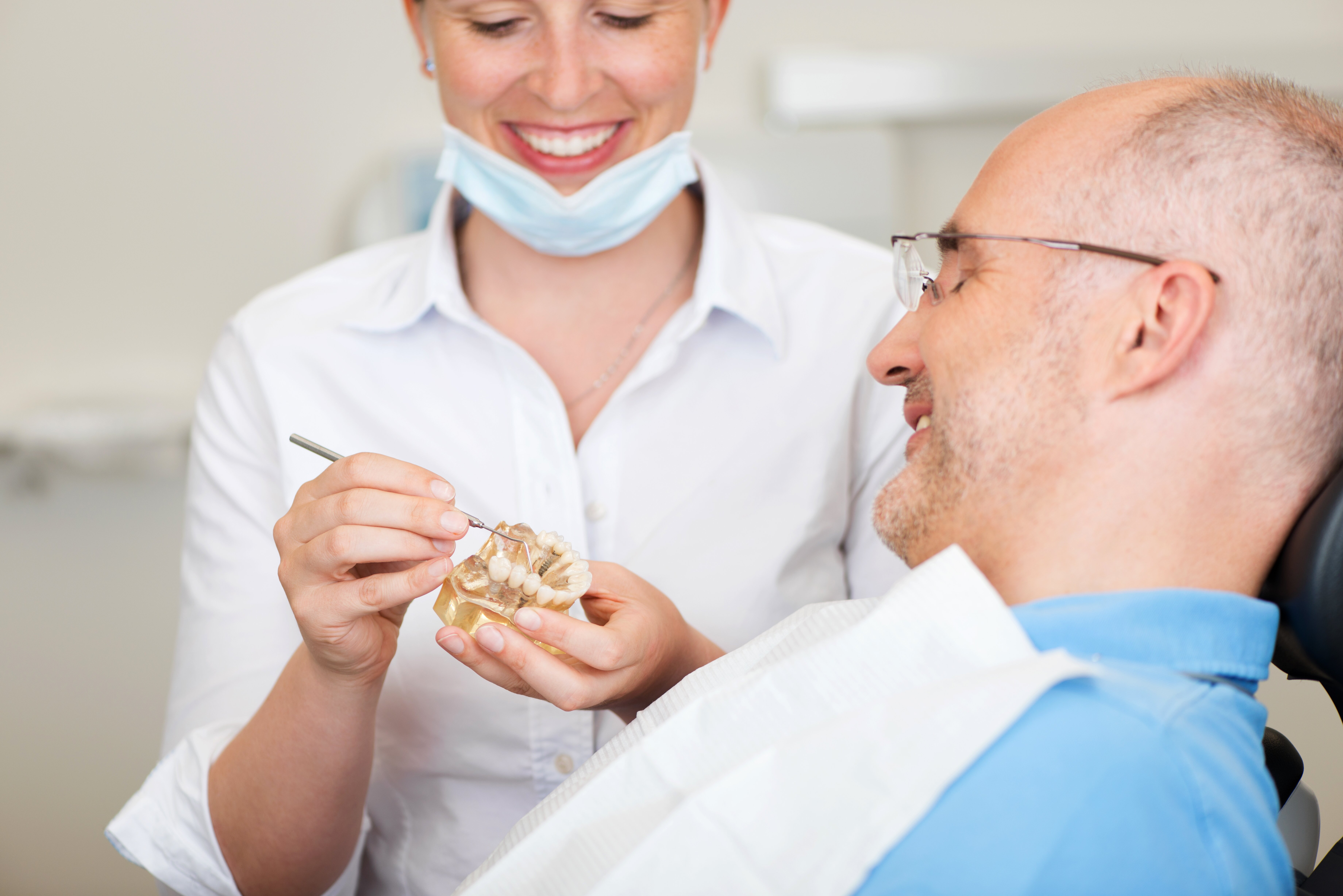 Dentist tinkering with a dental mould in front of a patient
