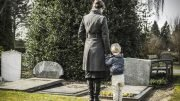 a mom and her son visiting a grave